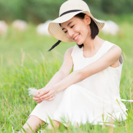 chinese girl with a straw hat, a man sitting on green grassland and enjoy the good times